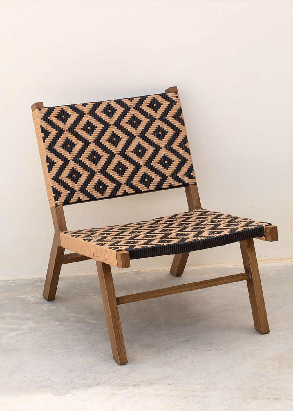 Black and natural diamond patterned synthetic woven outdoor lounge chair.